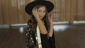 Little happy girl in costume of sorceress posing at camera. Portrait of little happy girl in costume of sorceress posing and flirting at camera. Full HD stock footage