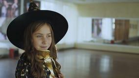 Little happy girl in costume of sorceress posing at camera. Portrait of little happy girl in costume of sorceress posing and flirting at camera. Full HD stock video
