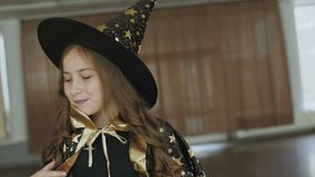 Little happy girl in costume of sorceress posing at camera. Portrait of little happy girl in costume of sorceress posing and flirting at camera. Full HD stock video footage