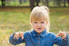 Happy girl in denim sweater plays in the park and shows emotions stock photos