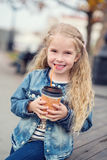 Little happy girl drinking cocoa out of the straw outdoors Stock Photography