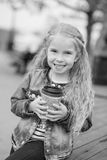 Little happy girl drinking cocoa out of the straw outdoors Royalty Free Stock Photos