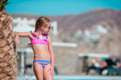 Little happy girl enjoy vacation near outdoor swimming pool Royalty Free Stock Photography