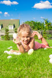 Little happy girl finding Easter eggs on green Royalty Free Stock Photography