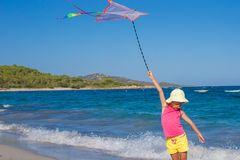 Little happy girl with flying kite on tropical Stock Image