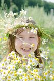 Little happy girl in a garland of field flowers. In the meadow royalty free stock images