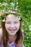 Little happy girl in a garland of field flowers. In the meadow royalty free stock photo