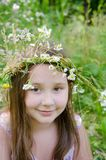 Little happy girl in a garland of field flowers. In the meadow royalty free stock photography