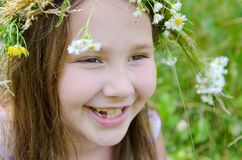 Little happy girl in a garland of field flowers. In the meadow stock photos