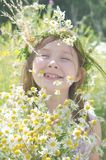 Little happy girl in a garland of field flowers. In the meadow royalty free stock image