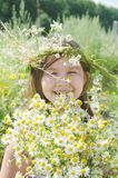 Little happy girl in a garland of field flowers. In the meadow royalty free stock photos