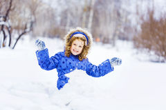 Little happy girl hand up and smiling, sitting in the snow park. Royalty Free Stock Image