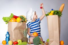 Little happy girl in the hat of the chef with big bags of food. A variety of fresh fruits and vegetables in bags on the table. Hea. Lth food. Child holding a royalty free stock photos