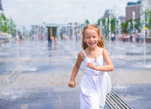 Little happy girl have fun in outdoor fountain Stock Image