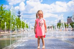 Little happy girl have fun in street fountain at Royalty Free Stock Photo