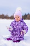 Little happy girl having fun on the snow at winter Stock Photos