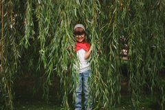 Little girl hiding in the willow foliage Royalty Free Stock Images