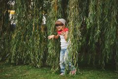 Little girl hiding in the willow foliage Stock Image