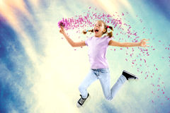 Little happy girl holding flowers while jumping Royalty Free Stock Photo