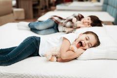 Little happy girl hugs bear lying on bed. In background little boy sleeps. royalty free stock photos