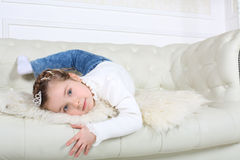 Little happy girl in jeans lies on white leather sofa Stock Photography