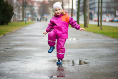Little happy girl jumping in puddle Royalty Free Stock Images