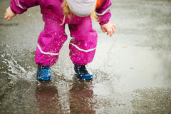 Little happy girl jumping in puddle Royalty Free Stock Photography