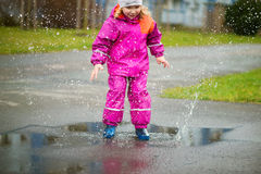 Little happy girl jumping in puddle Royalty Free Stock Image