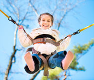Little happy  girl jumping on the trampoline Stock Photos