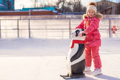 Little happy girl learning to skate on the rink Royalty Free Stock Image