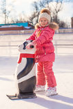 Little happy girl learning to skate on the rink Royalty Free Stock Photos