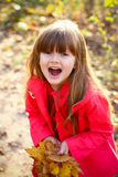 Little happy girl with leaves in autumn forest Royalty Free Stock Images