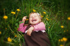 The little happy girl lies in a grass and laughs stock photo