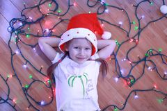 Little happy girl lies among the multi-colored. Lights on a wooden floor. This image has attached release Stock Images