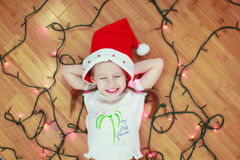 Little happy girl lies among the multi-colored. Lights on a wooden floor. This image has attached release Royalty Free Stock Photography