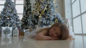 Little happy girl lies near the Christmas tree with gifts stock video footage