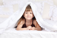 Little happy girl looks out from under blanket Stock Images