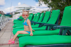 Little happy girl on the loungers by pool looking Stock Photography