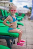 Little happy girl on the loungers by pool looking. At camera. This image has attached release royalty free stock image