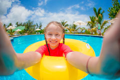 Little happy girl making selfie at inflatable rubber ring in swimming pool Royalty Free Stock Image