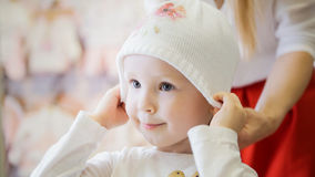 Little happy girl with mommy doing shopping and buying hat in kids dress store Royalty Free Stock Photo