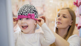 Little happy girl with mommy doing shopping and buying pink hat in kids dress store Royalty Free Stock Images