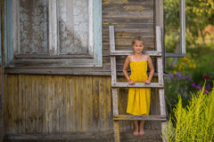 A little happy girl near the village house. Royalty Free Stock Images