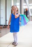 Little happy girl with packages in a large Stock Photo