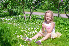 Little happy girl picking flowers in green glade Royalty Free Stock Images