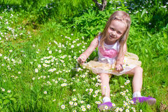 Little happy girl picking flowers in green glade Stock Images