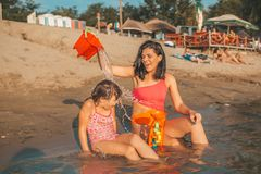 Little happy girl playing with beach toys and water with  her mother on beach royalty free stock photography