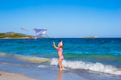 Little happy girl playing with flying kite on Royalty Free Stock Image