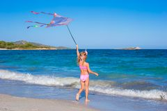Little happy girl playing with flying kite on Stock Photo