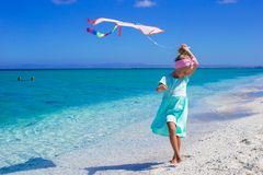 Little happy girl playing with flying kite on Stock Images